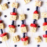 5 fruit kabobs with rice krispies treats and blueberries and extra rice krispies treats all around them on a white background