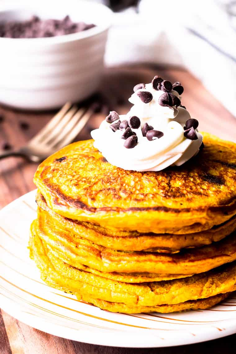 Close up of a stack of pumpkin chocolate chip pancakes topped with whipped cream and mini chocolate chips with a fork and white bowl full of chips faded in the background all over a wood background