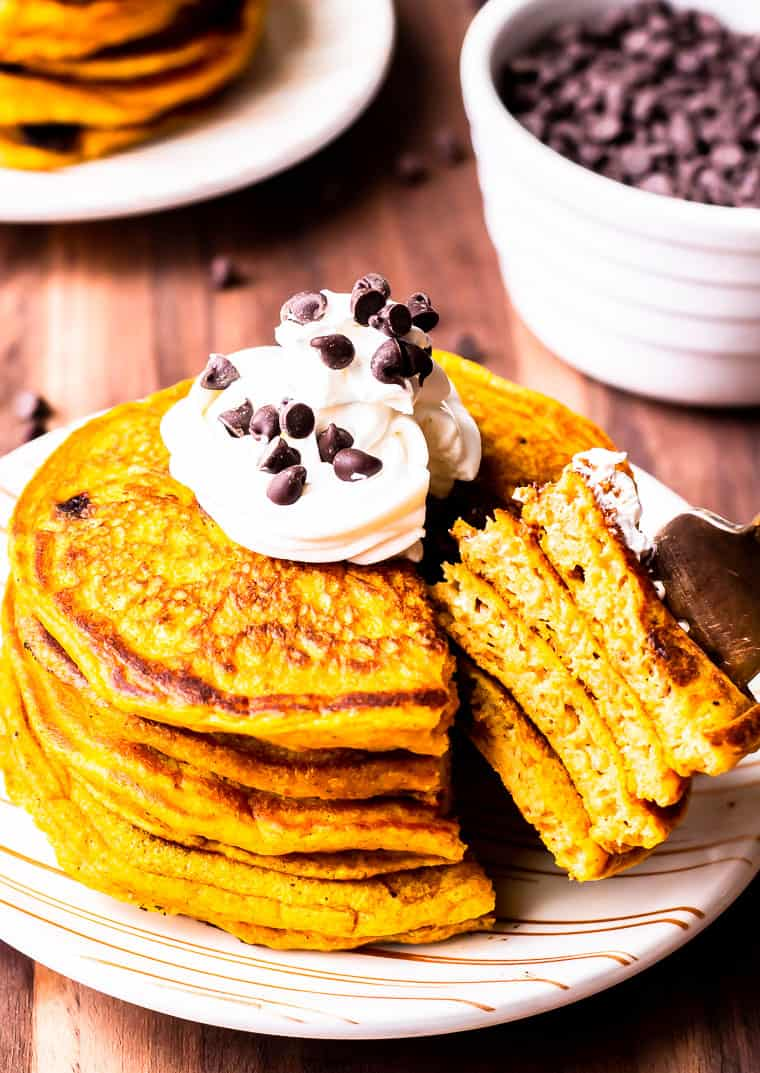 A stack of pumpkin chocolate chip pancakes with whipped cream and mini chips on top and a forkful being taken out with a second stack and bowl of mini chips in the background all over a wood background