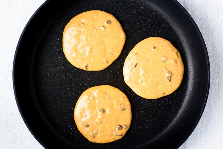 3 pumpkin chocolate chip pancakes cooking in a black skillet over a white background