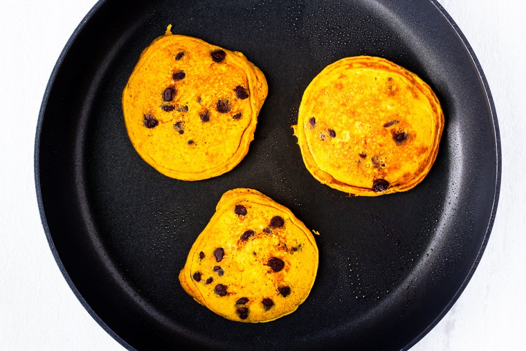 3 cooked pumpkin chocolate chip pancakes in a black skillet over a white background