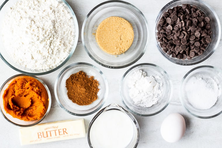 Ingredients needed to make pumpkin chocolate chip scones in glass bowls on a white background