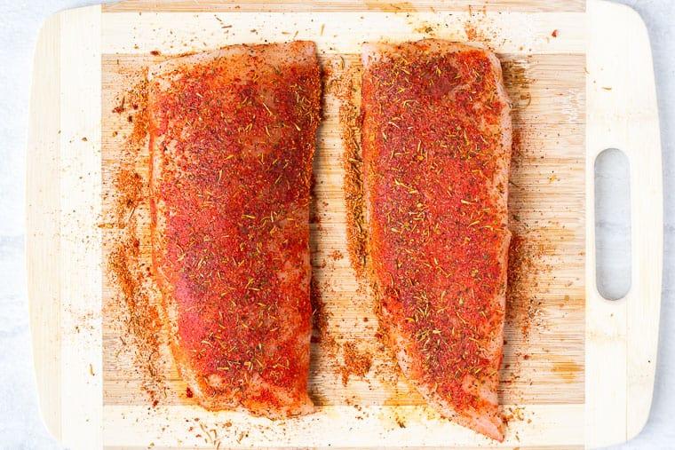 2 cod fillets with blackening seasoning on them on a cutting board