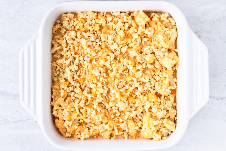 Baked cauliflower mac and cheese topped with almond four crumbs in a square, white baking dish