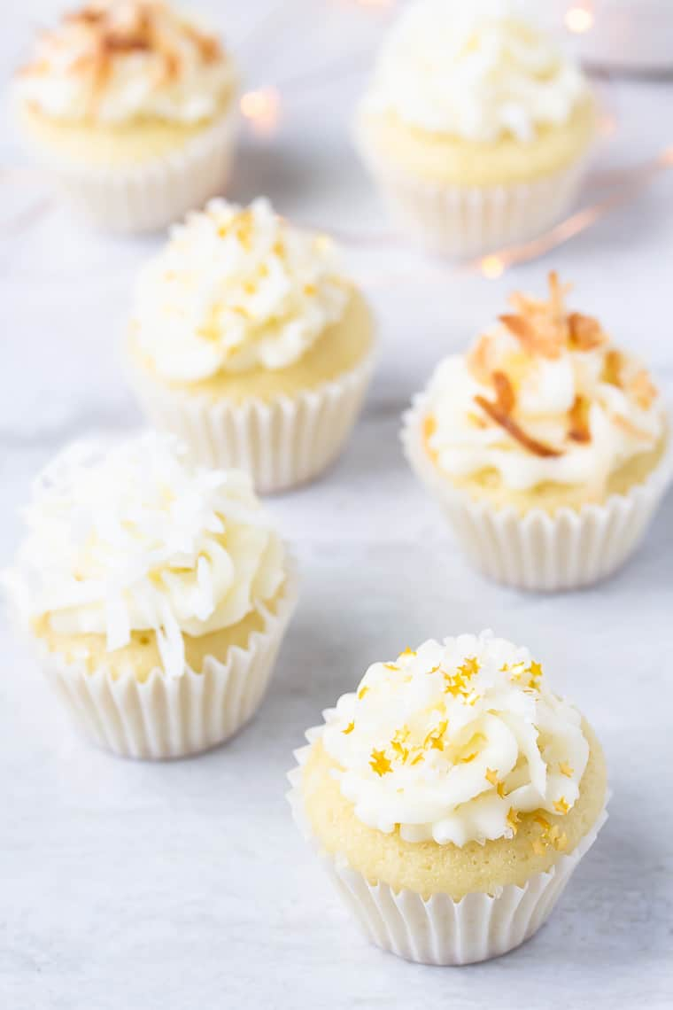 Mini coconut cupcakes staggered on a white background with blurred gold lights behind them