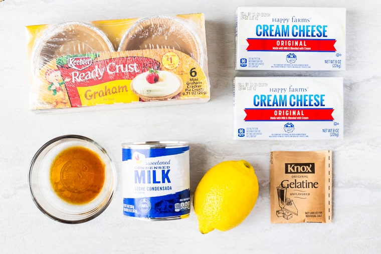 Ingredients needed to make no bake lemon cheesecake on a white background