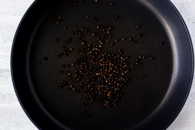 Black Peppercorns being toasted in a black skillet over a white background