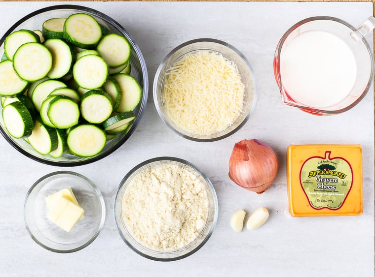 Ingredients to make zucchini gratin laid out on a white background