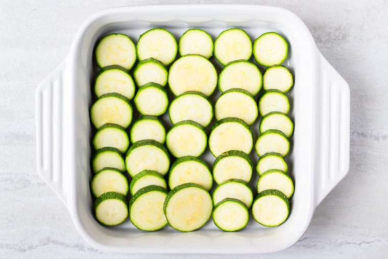 A layer of zucchini rounds in the bottom of a white casserole dish