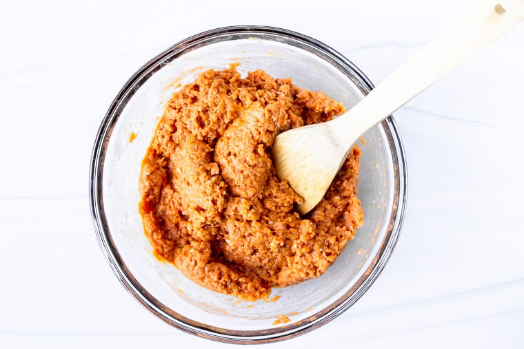 Keto buffalo chicken meatball mixture in a glass bowl with a wood spoon over a white background