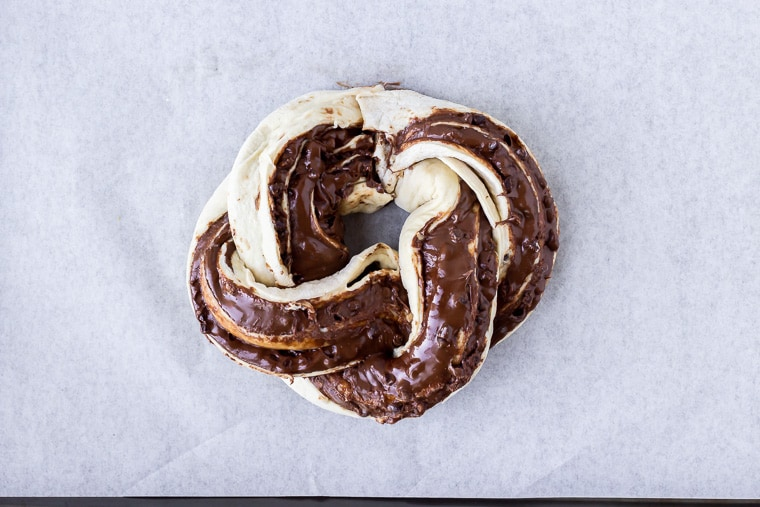 Babka dough formed in a circle on parchment paper on a baking sheet