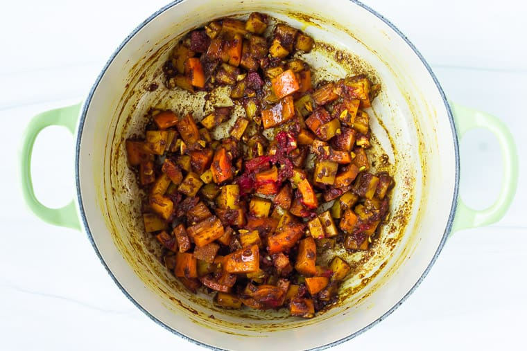 Peppers and seasonings cooking in a dutch oven over a white background