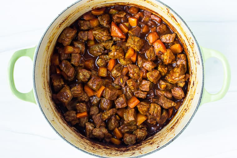 Beef, peppers, and curry spices cooking in a dutch oven over a white background
