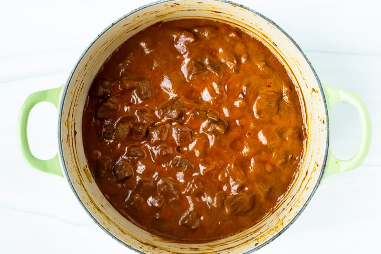 Coconut curry beef in a Dutch oven over a white background