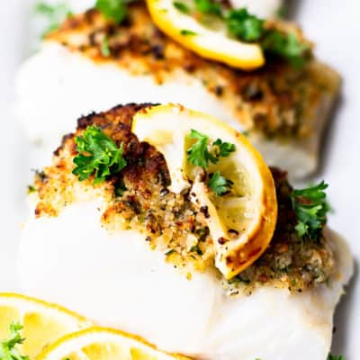 Close up of cod fillets with crispy breadcrumbs on top with lemon slices and fresh parsley all around