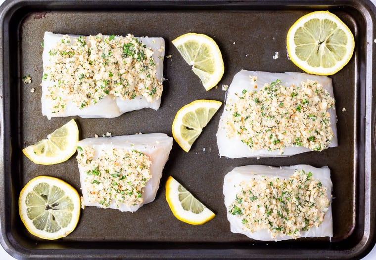 4 cod fillets on a baking sheet with breadcrumb topping and lemon slices around them