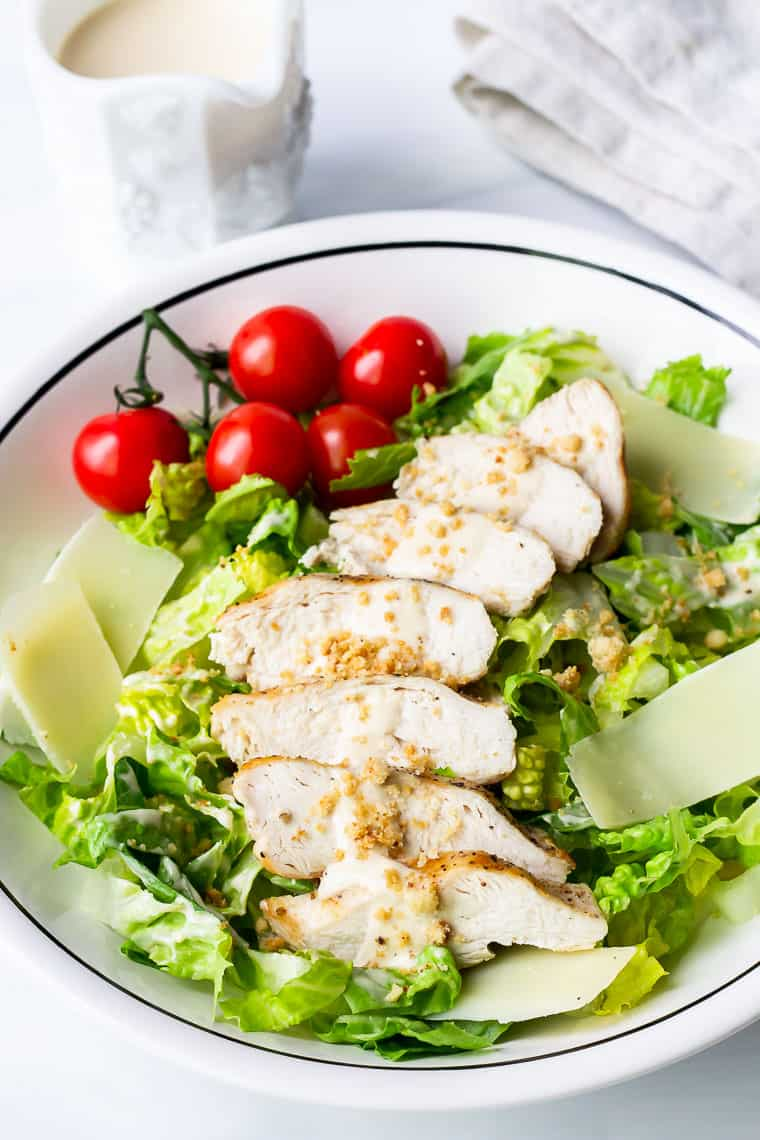 Grilled CHicken Caesar salad in a white bowl with a white container of caesar dressing and a napkin near it
