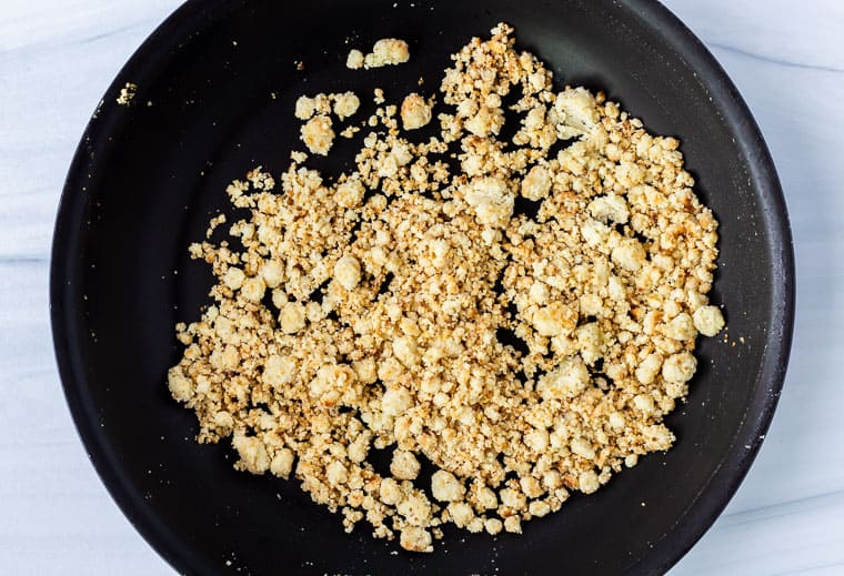 Toasted garlic almond flour crumbs in a black skillet