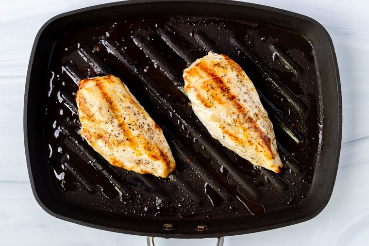 2 grilled chicken breasts in a grill pan