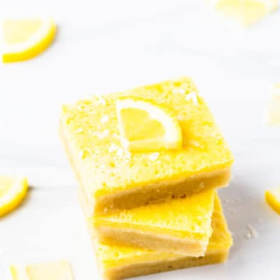 3 keto lemon bars stacked on top of each other with a lemon slice on top and a few more around them