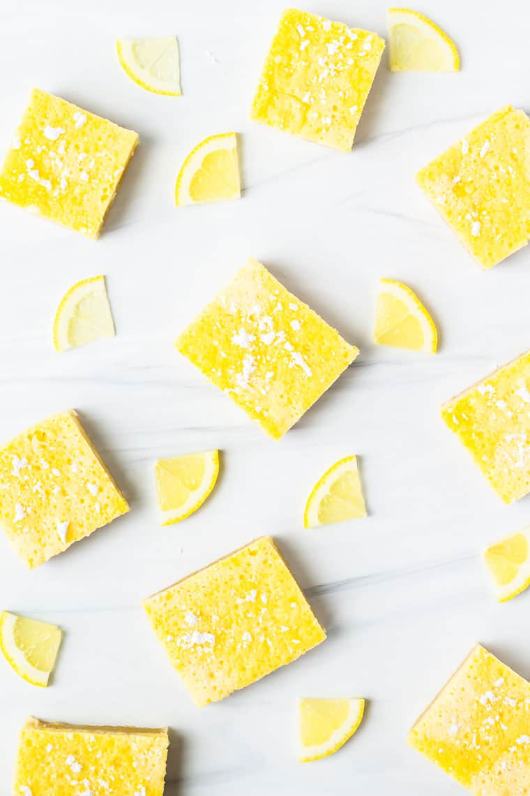 Overhead of scattered lemon bars and lemon slices over a white background