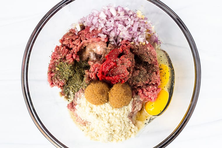 Meatloaf ingredients in a glass bowl on a white background