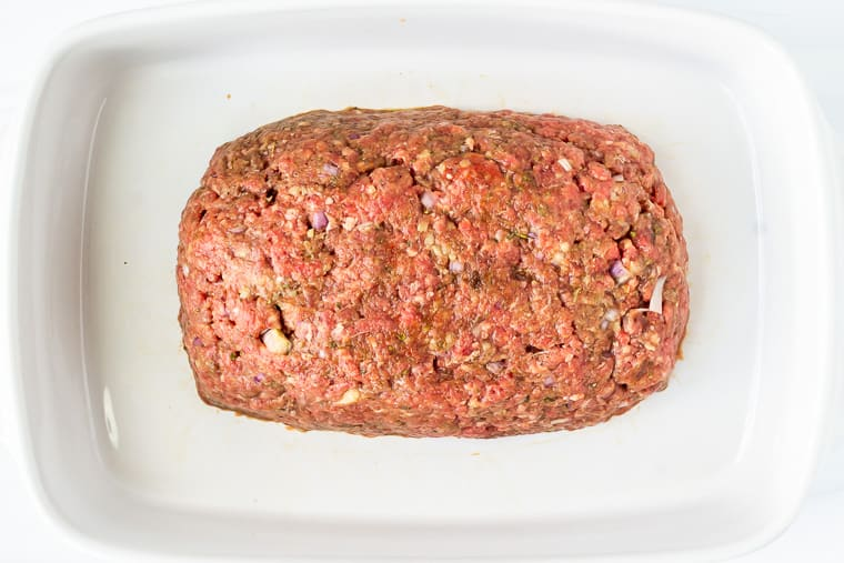 Raw meatloaf in a white baking dish