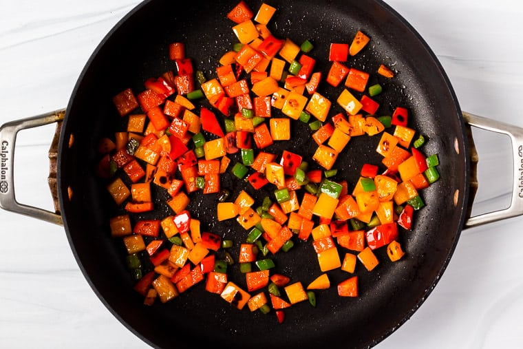 Mixed peppers cooking in a black skillet