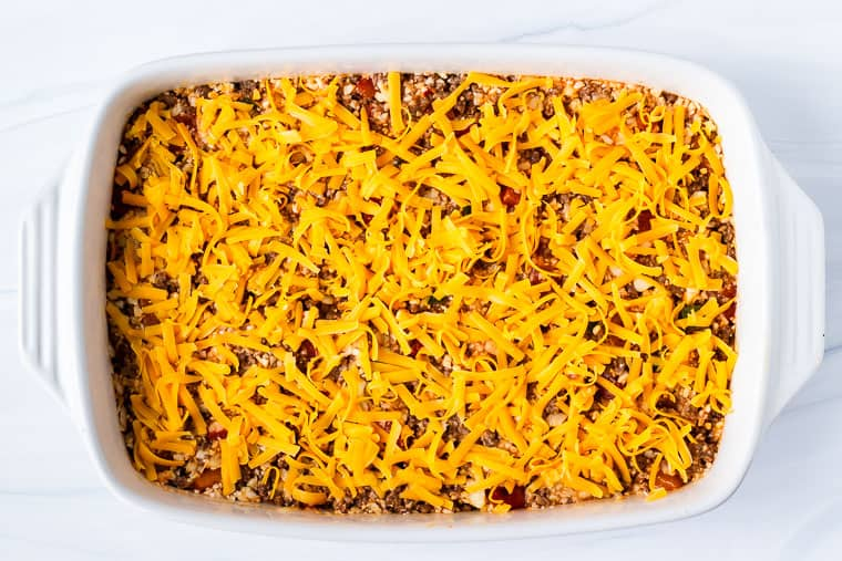 A large casserole topped with cheddar cheese