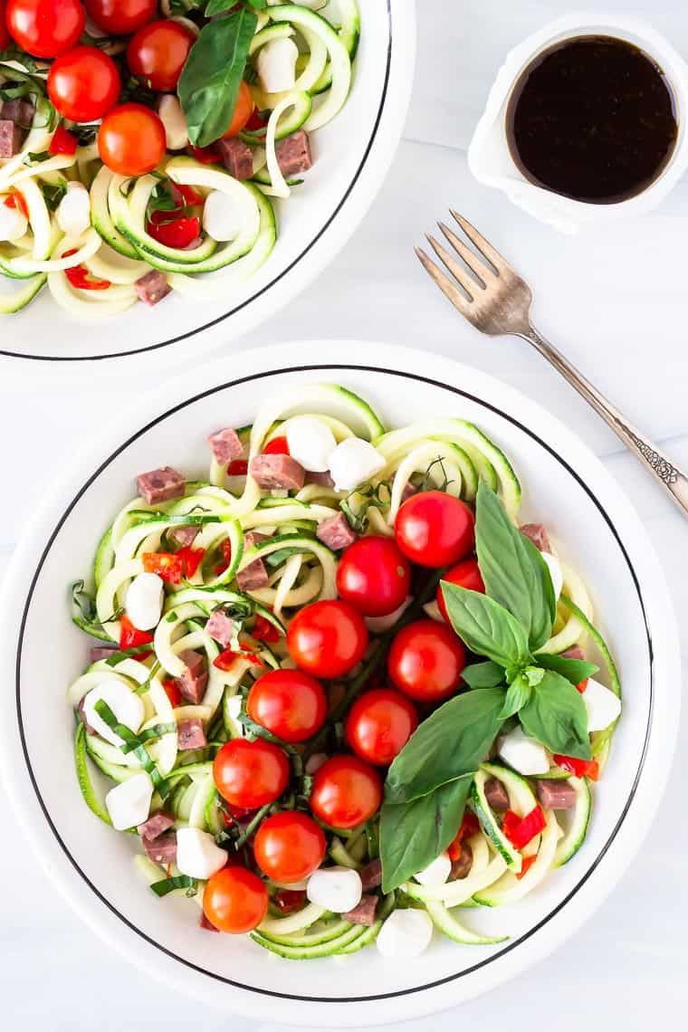 Overhead of 2 white bowls with zucchini keto pasta salad and a small pitcher of balsamic dressing and a fork next to them on a white background