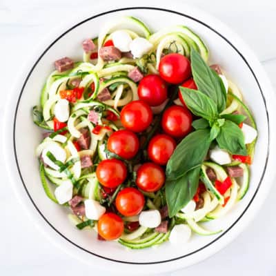 A zoodle pasta salad in a white bowl over a white background