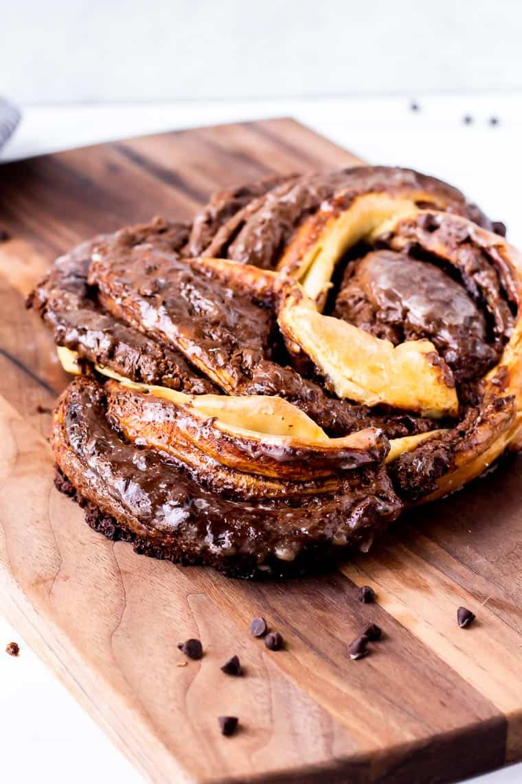 Nutella Babka Ring on a wood board with mini chocolate chips around it