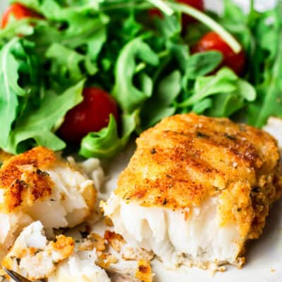 Pan fried cod on a plate cut in half with a fork and a salad