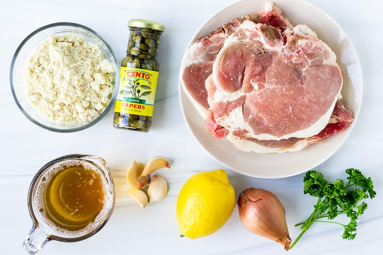 Ingredients needed to make pork piccata on a white background