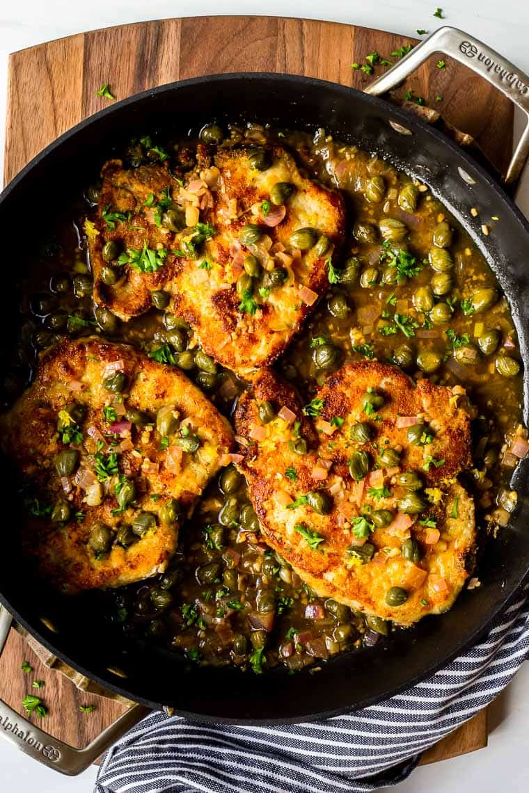 Overhead of pork piccata in a black skillet over a wood board with a blue and white napkin on the bottom