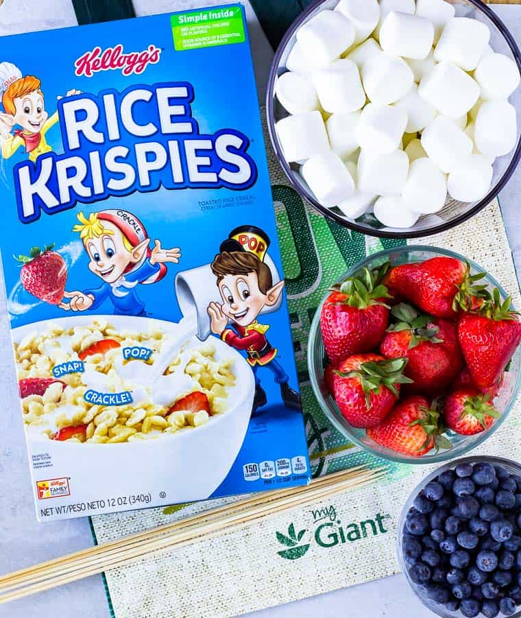 Ingredients to make fruit kabobs with rice krispies on a white background