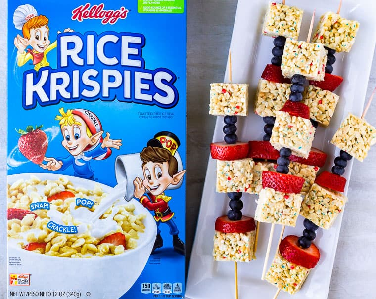 A box of rice krispies next to fruit kabobs on a white surface