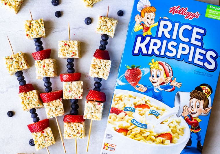 A box of rice krispies next to fruit kabobs with rice krispies treats and blueberries around them on a white background