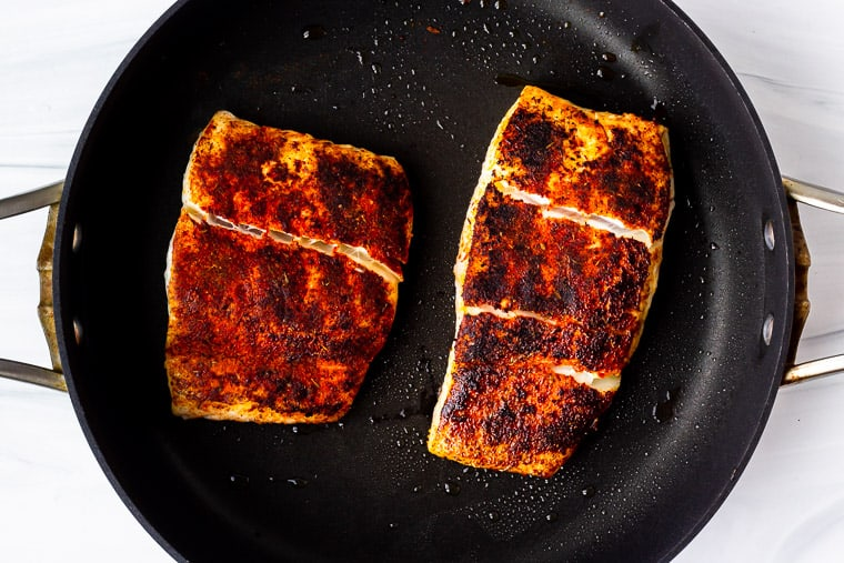 2 large halibut fillets cooking in a skillet with blackening seasoning on them