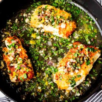 3 cod fillet in piccata sauce in a black skillet over a wood board with a blue and white striped towel around the bottom edge of the pan