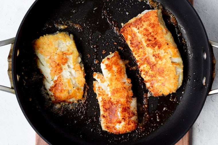 3 dredged cod fillets golden brown in a black skillet