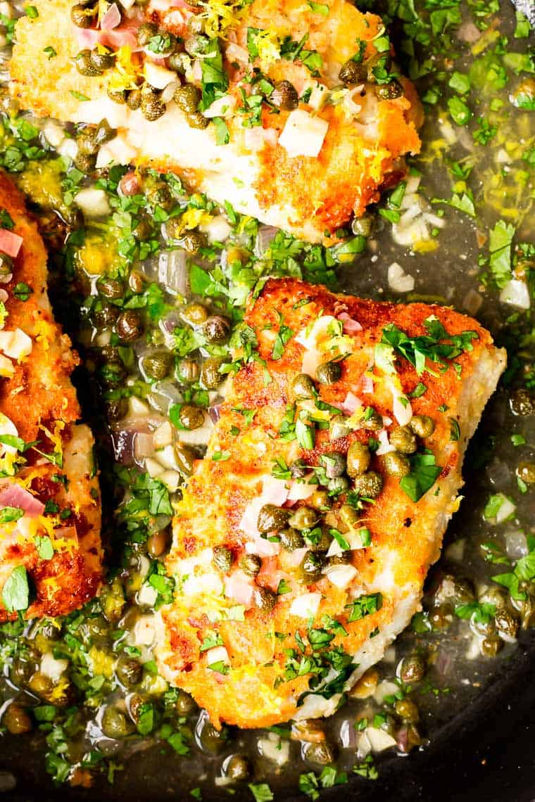 Golden cod fish fillets with piccata sauce close up in a black skillet