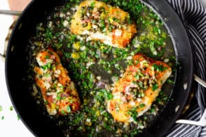 Cod Piccata topped with sauce and fresh parsley in a black skillet