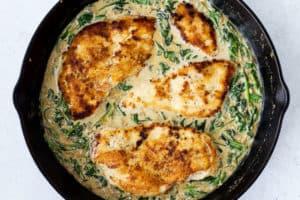 Chicken in spinach cream sauce in a cast iron skillet.