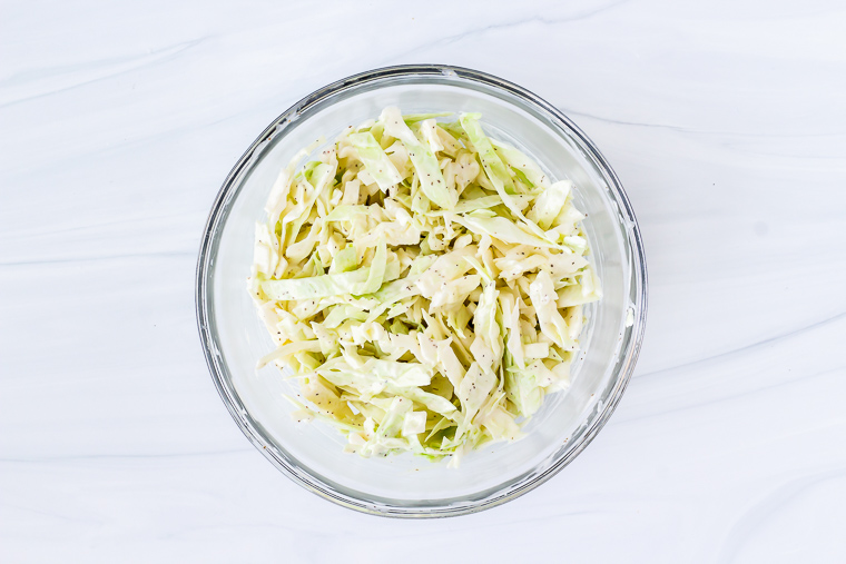 Keto coleslaw in a glass bowl over a white background