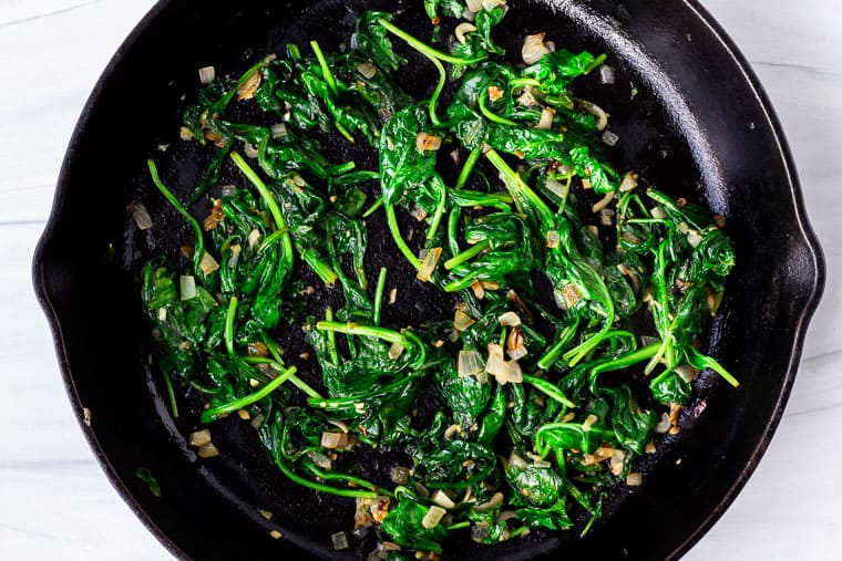 Cooked spinach with shallots and garlic in a black cast iron pan