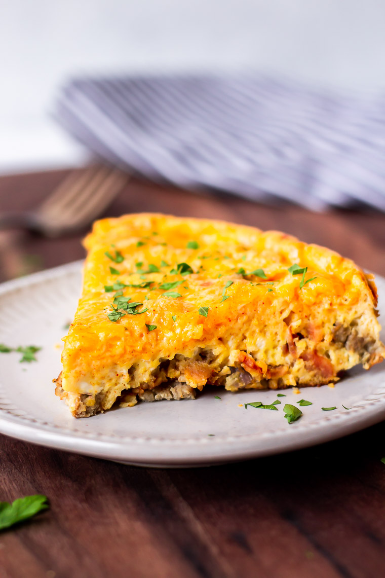 A slice of keto frittata on a white plate with a fork and towel blurred in the background