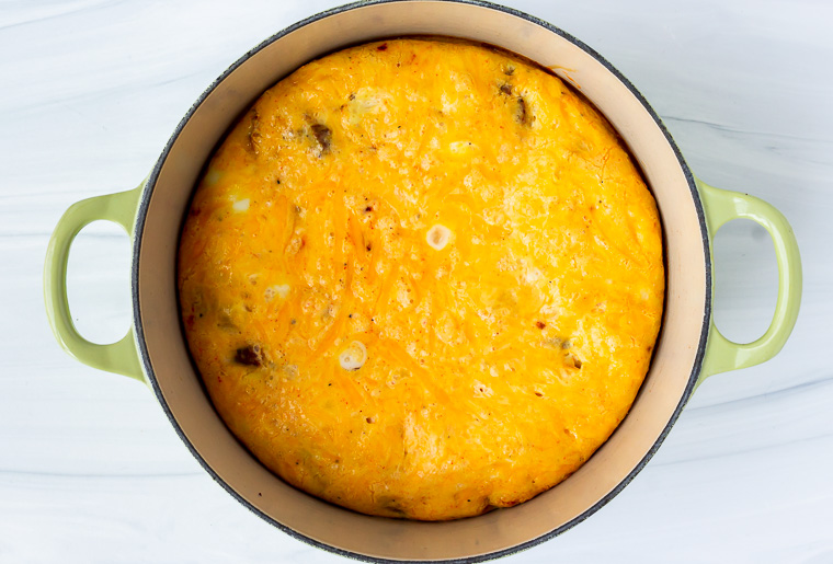 A baked keto frittata over a white background