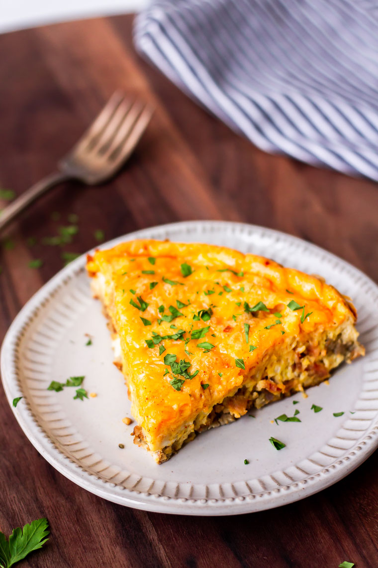 A slice of keto frittata on a white plate on a wood board with a fork and blue and white striped towel behind it