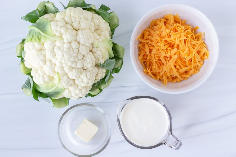 Ingredients to make cheesy cauliflower grits on a white background